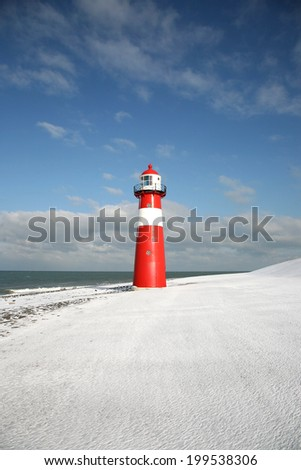 Red and white lighthouse on a dike in the snow - stock photo