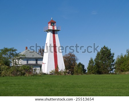 Red and white lighthouse on Prince Edward Island, Canada beside an old house, - stock photo