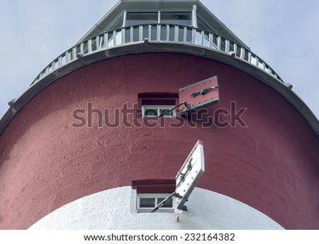 Red and white lighthouse photographed from below.