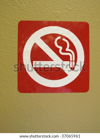 Red and white no smoking symbol sign on a wall.