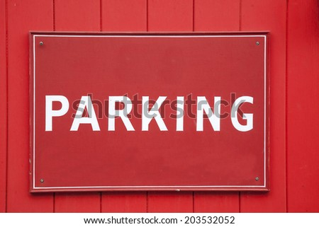 Red and White Parking Sign on Garage Door