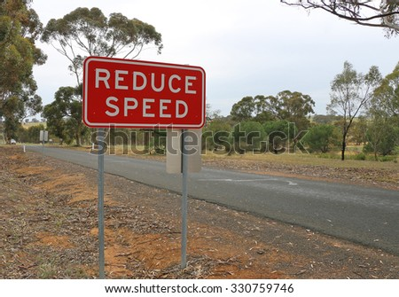 red and white Reduce Speed safety sign on a country road