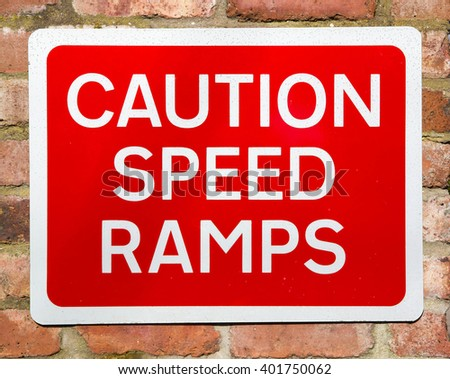 Red and white road sign with a warning of a speed ramps ahead concept against a brick wall background - stock photo