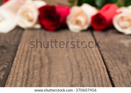 Red and white roses on a light wooden background. Women' s day, Valentines Day, Mothers day. Copy space, selective focus. Natural optical blur.