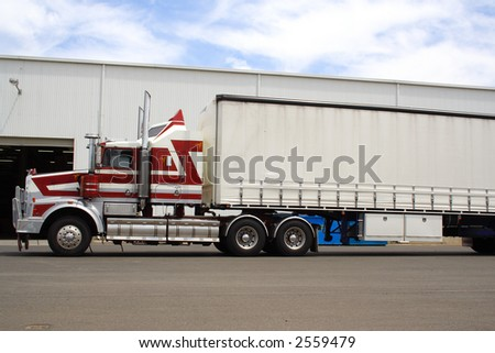 Red and white semi truck - stock photo