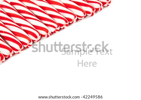 Red and white striped candy canes on a white copy space