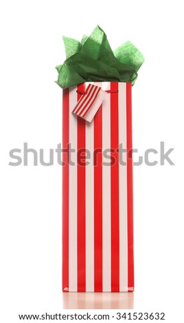 Red and white striped Christmas wine gift bag with bright green tissue and gift tag. On white background with soft shadow.