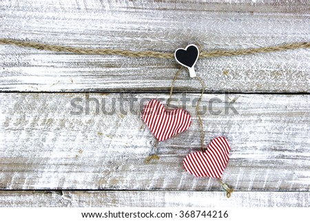 Red and white striped fabric hearts hanging on clothesline with whitewash rustic antique wood background; Valentine's Day and love concept - stock photo