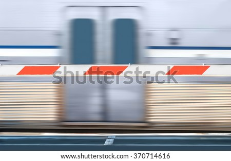 Red and white striped train crossing barrier and speeding urban commuter train. Focus on barricade. Train doors and motion blur background.  - stock photo