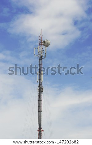 Red and White Telecommunication tower with blue sky and cloud background