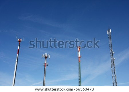 Red and white tower of communications with with a lot of different antennas under clear sky. - stock photo