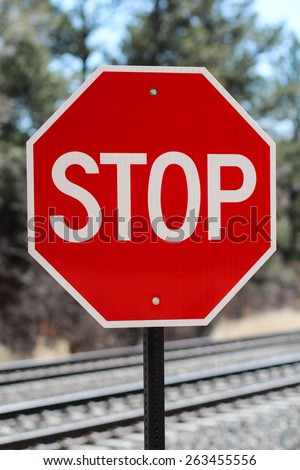 Red And White Traffic Stop Sign Placed Near Train Tracks In Colorado Springs, Colorado Against Forest Background - stock photo