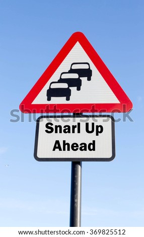 Red and white triangular road sign with a Snarl Up Ahead concept against a partly cloudy sky background - stock photo