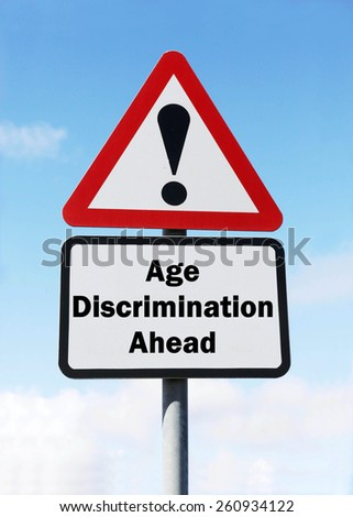 Red and white triangular road sign with warning of Age Discrimination ahead concept against a partly cloudy sky background