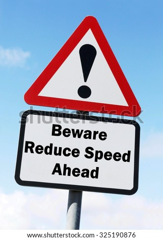 Red and white triangular road sign with warning to Beware to Reduce Speed ahead concept against a partly cloudy sky background - stock photo
