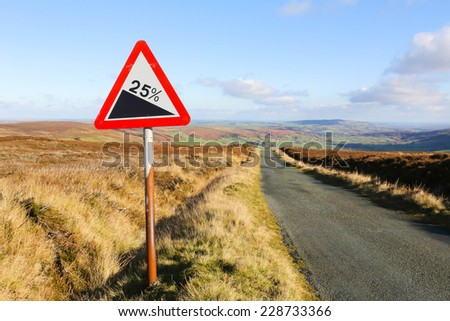 Red and white triangular warning road sign indicating a steep hill with a 25% slope ahead on a moorland road, - stock photo