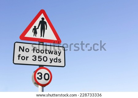 Red and white triangular warning road sign indicating pedestrian walkway, no footway for 350 yards with a 30 miles per hour speed limit sign below.. - stock photo