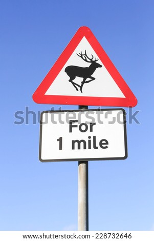Red and white triangular warning road sign indicating the danger of deer on the road for one mile.