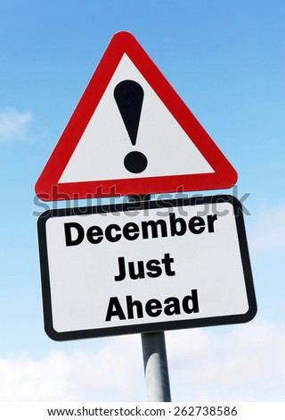 Red and white triangular warning road sign informing that December is Just Ahead concept against a partly cloudy sky background - stock photo