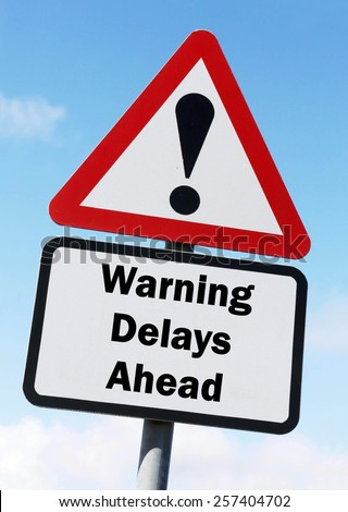 Red and white triangular warning road sign with a warning of a Delays ahead concept against a partly cloudy sky background - stock photo