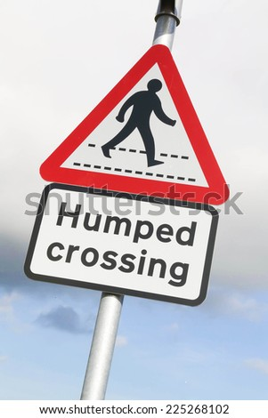Red and white triangular warning road sign with a warning of a Humped Pedestrian Crossing ahead concept against a partly cloudy sky background - stock photo