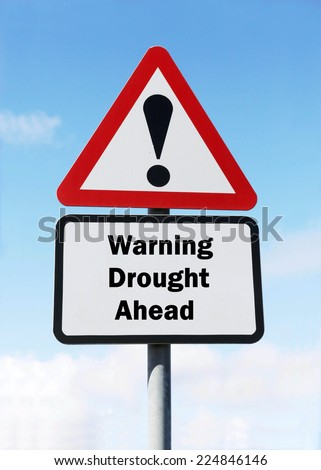 Red and white triangular warning road sign with a warning of Drought ahead concept against a partly cloudy sky background - stock photo