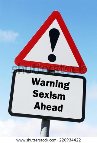 Red and white triangular warning road sign with a warning of sexism ahead concept against a partly cloudy sky background - stock photo