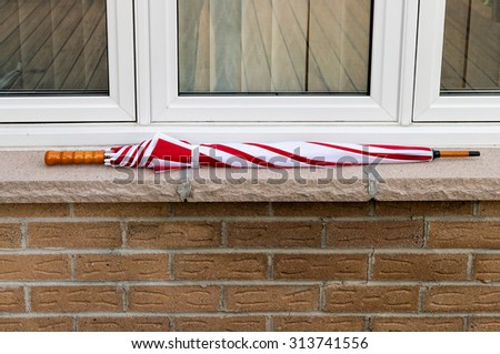 Red and White umbrella on a window ledge - stock photo