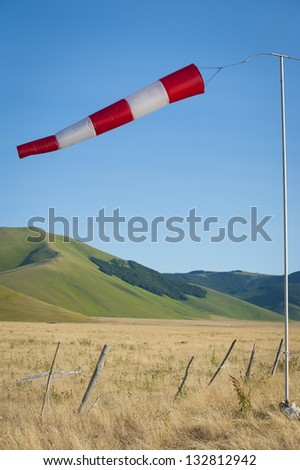 Red and white windsock blows against a blue sky. Castelluccio di Norcia, Italy.
