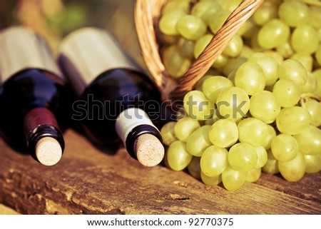 Red and white wine bottles and bunch of grapes in basket on wooden table. Retro toned image - stock photo