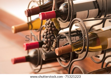 Red and white wine bottles stacked on iron racks shot with limited depth of field
