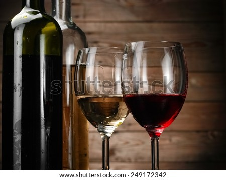 Red and white wine glasses and bottles, close up - stock photo