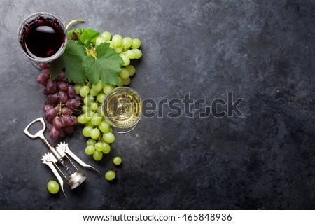 Red and white wine glasses and grape over stone table. Top view with copy space