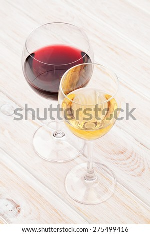 Red and white wine glasses on white wooden table - stock photo