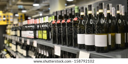 Red and white wine in bottles in wine shop