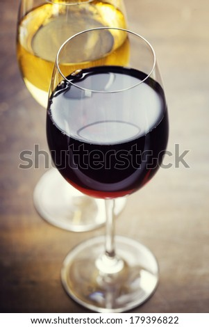 Red and white wine on old wooden table - stock photo
