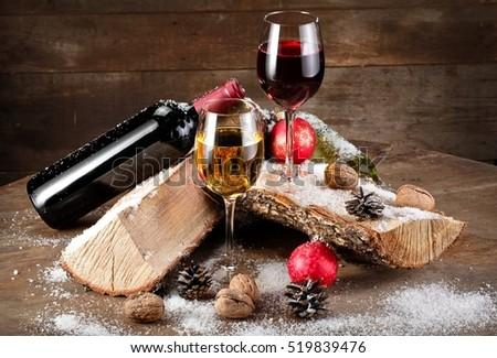 Red and white wine on wood with snow