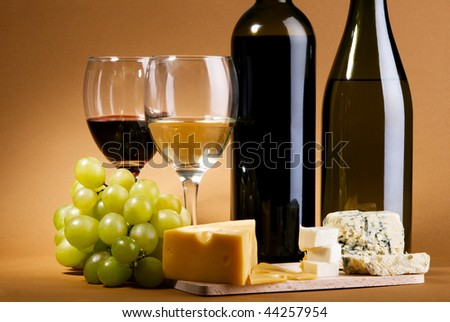 Red and white wine with different sorts of cheese - stock photo