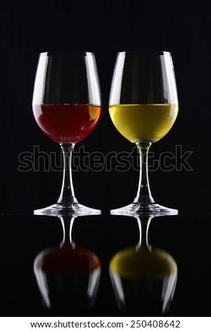 Red and white wineglasses isolated on black background - stock photo