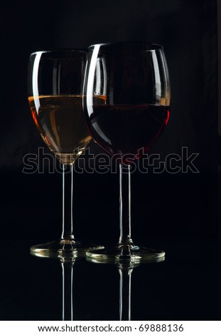Red and white wineglasses shot on a black background - stock photo