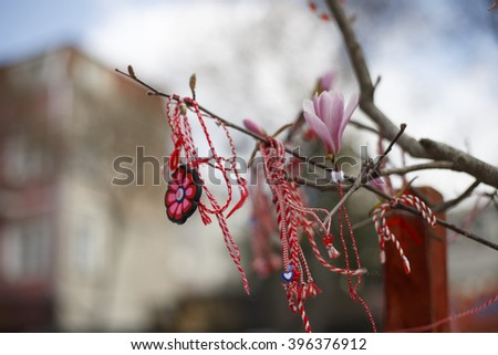 """Red and white woven threads symbolizing Mother Nature and the wish for good health in the Bulgarian tradition called """"Martentisa"""" or Grandma March - tied on tree branches in Spring - stock photo"""