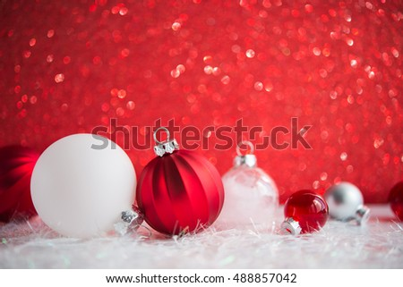 Red and white xmas ornaments on red glitter bokeh background. Merry christmas card. Winter holiday theme. Happy New Year. Space for text.