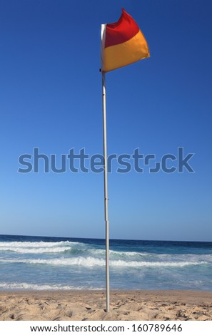 Red and yellow beach flag flapping in the breeze.