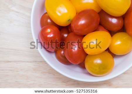 Red and yellow cherry tomatoes in a bowl.