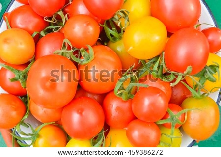 red and yellow cherry tomatoes on the plate on a wooden background