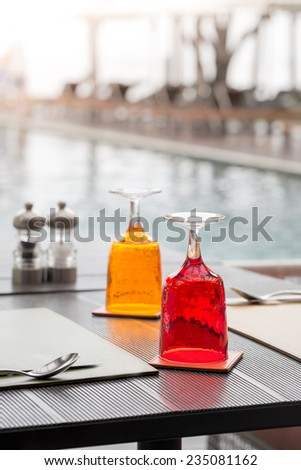 Red and Yellow Glass of water on luxury table setting near swimming pool, selective focus with bokeh background