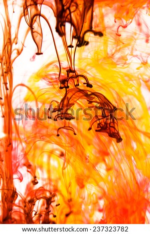 Red and yellow liquid in water making abstract forms - stock photo