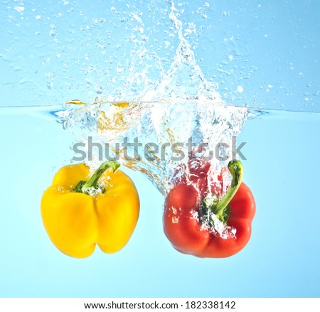 red and yellow pepper splashed into water - stock photo