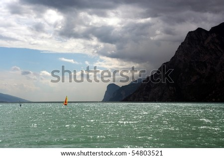 Red and yellow sail windsurfer on a lake with mountains as a background - stock photo