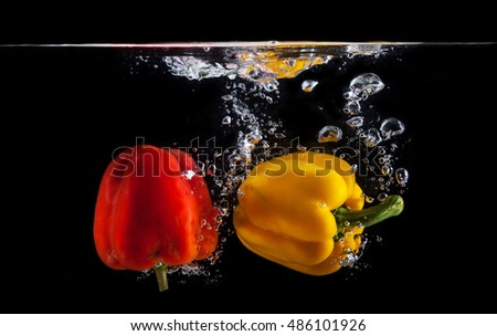 Red and yellow sweet pepper splash into a black color of water